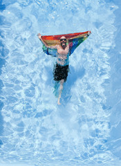 Gay man with gay pride flag in swimming pool.