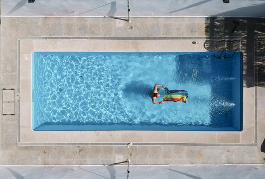 Gay man with gay pride flag in swimming pool
