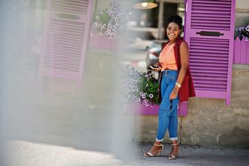 African american girl posed against purple windows outdoor.