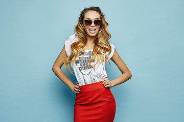 Beautiful, emotional and fashionable blonde model girl in white t-shirt, in red skirt and stylish sunglasses smiling and posing in studio at blue background