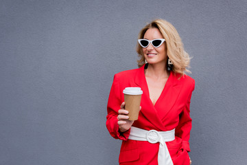smiling attractive woman in red jacket holding disposable coffee cup on street