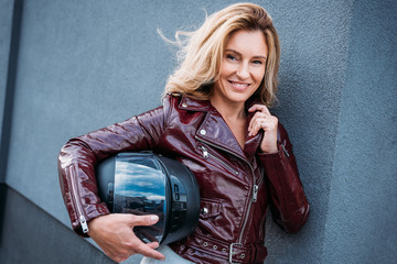beautiful woman in leather jacket holding motorcycle helmet on street and looking at camera
