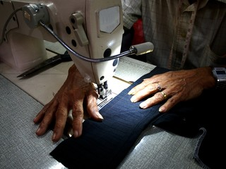 Hands of a tailor working on a sewing machine