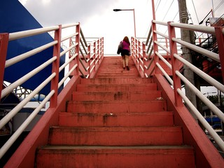 Woman climbing up the steps of a footbridge