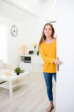 cheerful young woman welcome friends at open front door new student home apartment