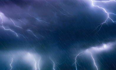 Powerful lightnings and rain in dark stormy sky, weather forecast concept, climate change background