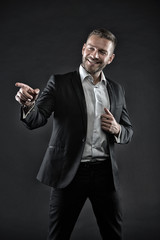 Man with big smile on face isolated on black background. Guy with three day beard wearing smart suit and white shirt. Comedian doing performance, fun concept. Office clerk with cool gesture