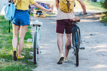 partial view of couple with backpacks and bicycles in park