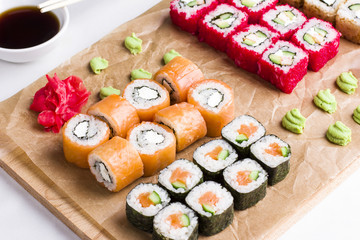 Set of different types of Japanese sushi rolls on wooden Board