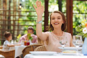 Lifting hand. Smiling dark-eyed woman wearing stylish beige dress lifting her hand calling waitress