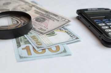 The concept of lending. Money, calculator, magnifier.
