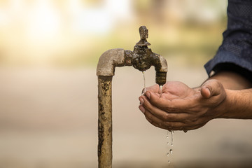 Cupped Hands under falling water from old rusty tap. selective focus, shallow depth of field.