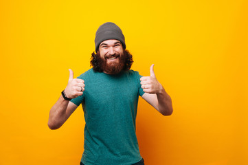 Happy smiling bearded hipster man showing thumbs up over yellow background