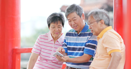 Senior old friends looking at mobile phone together at outdoor