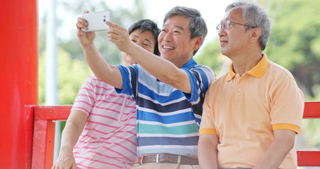 Senior friends talk together and take selfie with mobile phone at outdoor park