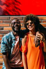 Black couple standing near brick wall