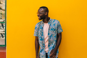 Cheerful black man portrait on yellow wall
