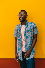 Cheerful black man portrait on yellow wall