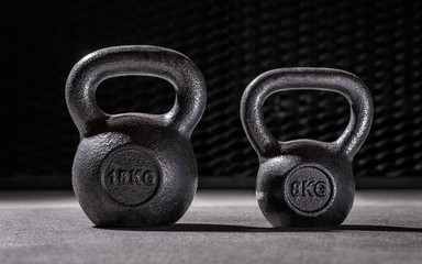 Two dumbbels with steel background in sportclub, 16kg and 8 kilograms