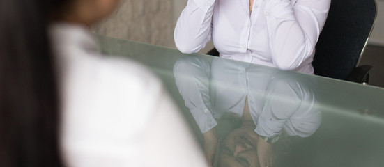 Woman crying after fired from job in glass table reflection