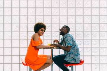 Cheerful African-American couple in cafe laughing