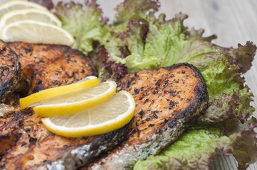 Fried salmon on a white plate decorated with lemon and salad