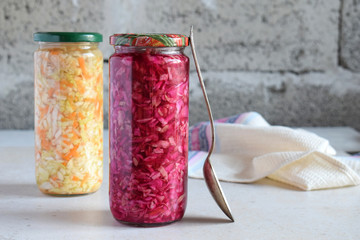 Sauerkraut in glass jar, marinated cabbage, carrot and beetroot. Probiotic and fermented food. Pickles. Canned vegetarian food concept.