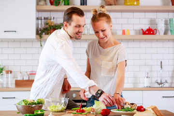 Photo of loving couple cooking vegetables in kitchen
