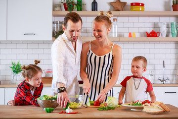 Picture of young parents with son and daughter preparing breakfast
