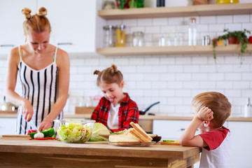 Photo of beautiful woman with her daughter and son cooking food in kitchen