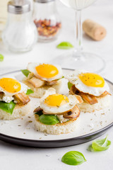 Canapes with fried mushrooms, quail egg, soft cheese and basil, beautiful appetizer for home party or event