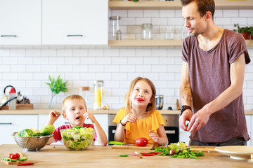 Picture of young father with daughter cooking vegetables