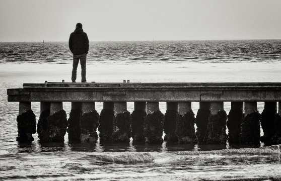 Lonely man standing on a pier staring at the sea