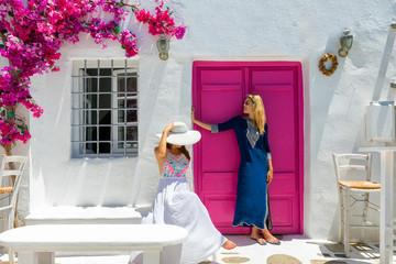 Attraktive, weibliche Touristinnen in Sommerkleidern stehen vor einer typischen Kulisse auf den...