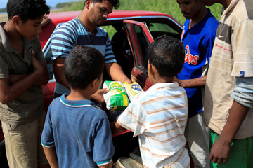 A child receives packages of corn flour in exchange for fish in Rio Chico