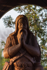 Wooden figure of Saint Onufr standing in a chapel near the road. Closeup