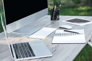 selective focus of laptop, textbook, digital tablet and computer on table outdoors