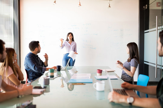 Woman giving presentation to her colleagues at office