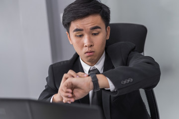 business man checking time on watch while using laptop