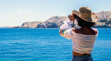 Frau schaut mit Fernglas aufs Meer