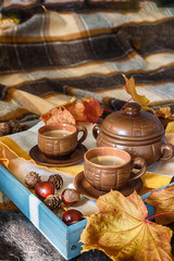 Cup of coffee on a tray on a bed with a soft cozy rug in the fall, the concept of breakfast in bed in style lagom