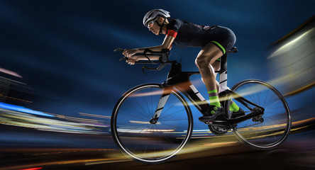 Aluminium Prints Cycling Sport background. Athletic woman cycling road bike in the evening. Dramatic view of the night city.