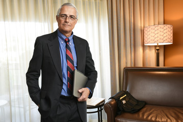 A senior businessman in his hotel room