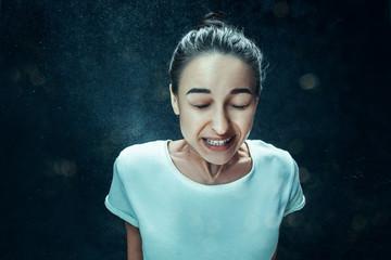 Young woman sneezing, studio portrait