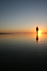 Silhouette of a woman walking on a beach with her reflection in the water