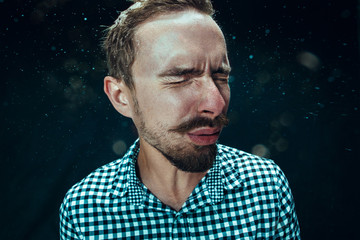 Young handsome man with beard sneezing, studio portrait