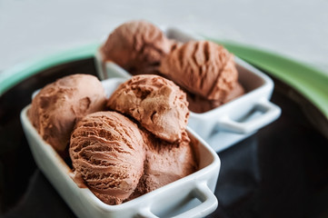 Ice cream as a background. Chocolate ice cream balls, structure, texture. Frozen cocoa in a beautiful white dish