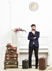 Macho elegant on thoughtful face standing near pile of vintage suitcase. Luggage and travelling concept. Man, traveller with beard and mustache with luggage, luxury white interior background.