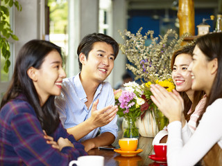 happy young asian adults chatting in coffee shop