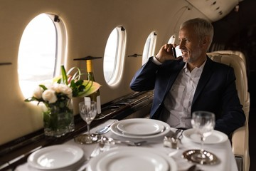 Businessman talking on mobile phone in private jet